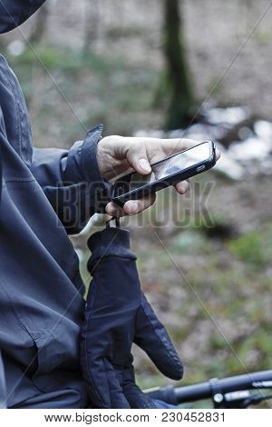 Man Hand Is Standing With A Bicycle And Holding Smart Phone Device In The Forest