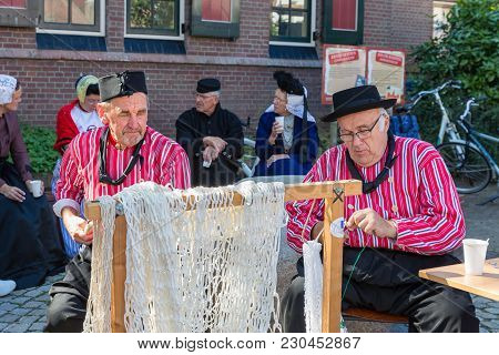Urk, The Netherlands - September 02, 2017: Two Men In Traditional Clothing Mending Fishing Nets At A