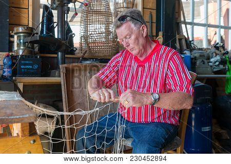 Urk, The Netherlands - September 02, 2017: Man In Traditional Dutch Costume Mending Fishing Nets In