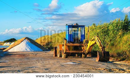 Tractor And Heaps Of Salt At The Salt Evaporation Pond In Marsala, Sicily Island, Italy