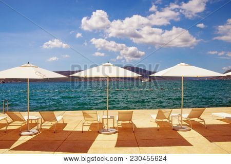 Summer Vacation. Sun Umbrellas And Chaise Lounges On The Beach. Montenegro, Bay Of Kotor, Tivat City