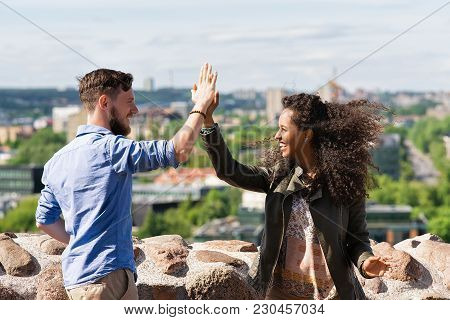 Young Smiling Multiracial Couple Clapping Their Hands As Diversity Friendship And Togetherness Conce