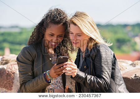 Caucasian And Middle Eastern Female Friends Looking Photos In The Mobile Phone As Diversity Friendsh