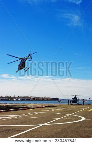 Black Helicopter Taking Off From Helipad In Lower Manhattan In New York, The Usa, On East River. Pie
