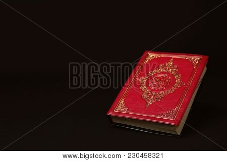 Holy book of Muslims on black background