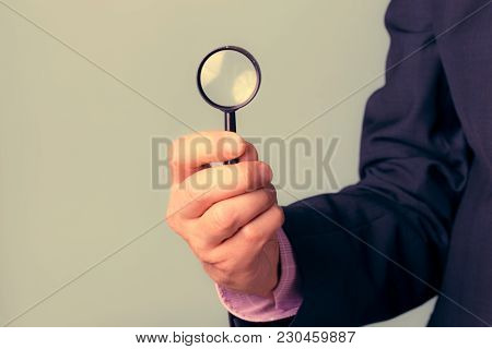 A Man Holds A Magnifying Glass In His Hand As A Symbol Of Observing Trends.