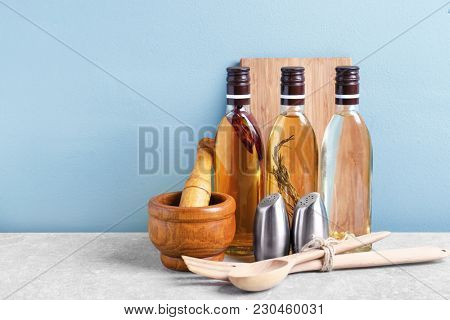 Cooking utensils and bottles with oil on table