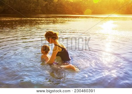 Mother Teaches A Child To Swim Outdoors. Little Boy Learning To Swim. The Concept Of Swim Lesson And