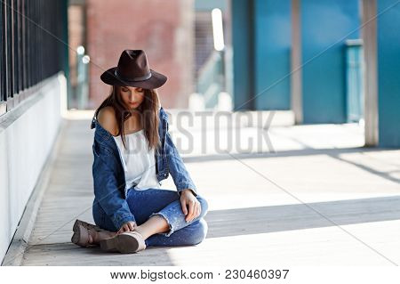 Young Woman Sprained Her Legs. Sad Girl Sitting On The Ground And Touching Her Ankle. Copy Space For