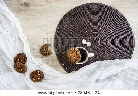 On A Wooden Table On A White And Dark Round Napkin Lie Oatmeal Cookies Sunflower Seeds Are A Glass O