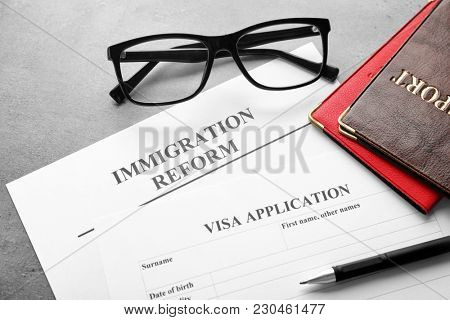 Passports, glasses and visa application form on table. Immigration reform
