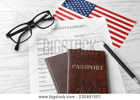Passports, application form and American flag on table. Immigration to USA
