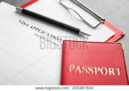 Passport and visa application form on table. Immigration reform