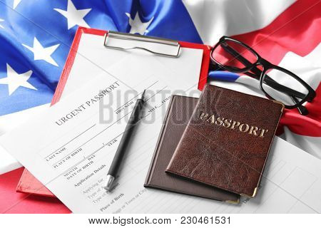 Passports and application form on American flag. Immigration to USA