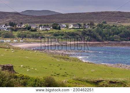 Laide, Scotland - June 8, 2012: Blue Atlantic Ocean  Beach With White Houses Build In Green On Top O