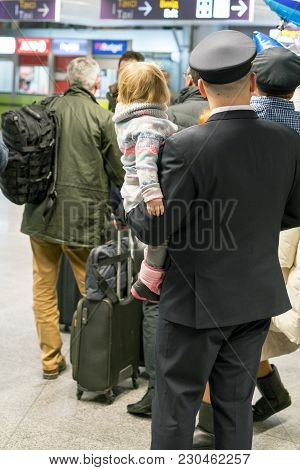 Pilot With His Family At The Airport. The Child Is In The Hands Of The Pope