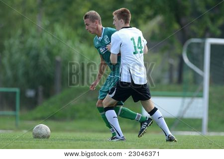 KAPOSVAR, HUNGARY - AUGUST 27: David Pinter (white 14) in action at the Hungarian National Championship under 18 game between Kaposvar (green) and Gyor (white) August 27, 2011 in Kaposvar, Hungary.