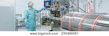 Pharmaceutical Technician In Sterile Environment Working With Equipment At Pharmacy Industry