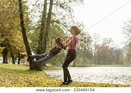 Happy Fit Young Mother Playing With Her Son At The Edge Of A Lake In Autumn Swinging Him Around In H