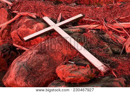 Hammer And Nails Next To A White Cross On A Red Lighten Rocks And Wood.