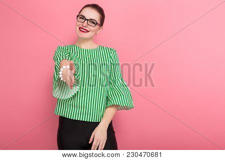 Portrait Of Attractive Businesswoman With Hair Bun In Striped Blouse And Eyeglasses Giving Hand For
