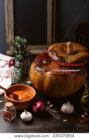 Pumpkin Cream Soup Poured Into A Baked Pumpkin. Still Life In A Rustic Style. Pumpkin Seeds And Spic