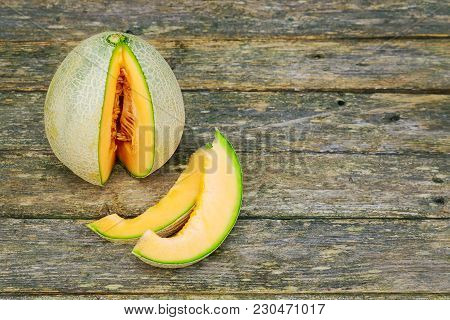 Fresh Honeydew Melon On Wooden Table, Healthy Food. Sliced On Wooden Table