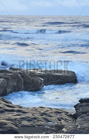 Moody Ocean Seascape With Landscape Of Rocky Beach During High Tide