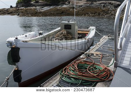 A White Utility Boat With Plenty Of Rope And Hoses Is Tied To A Dock Off Of The Coast Of Bar Harbor