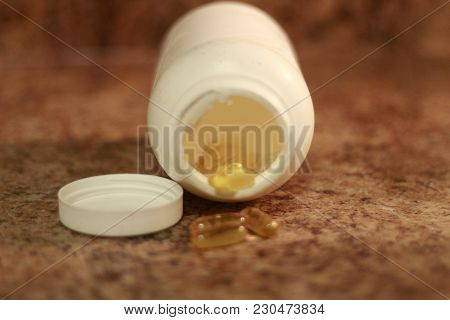 Capsules Of Fish Oil Spilled Out Open Container. Some People Believe That Fish Oil Helps With Heart