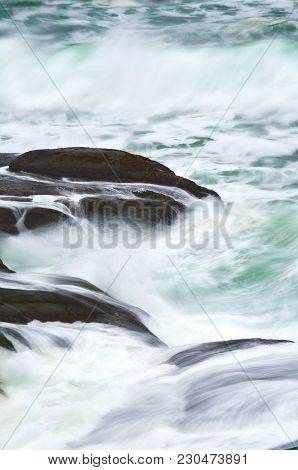 Closeup Of Blue Green Ocean Waves And Rocks During High Tide