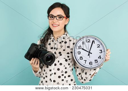 Portrait Of Young Attractive Woman Photographer In White Shirt And Glasses Holding Camera And Watche