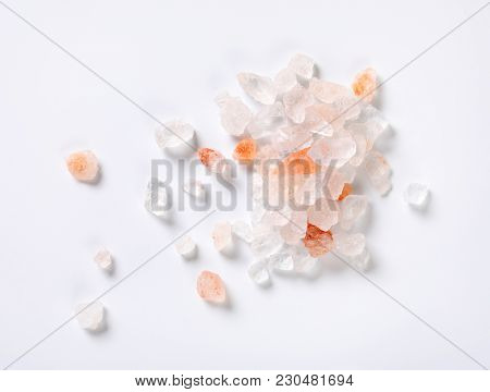 fingerful of coarse grained salt on white background