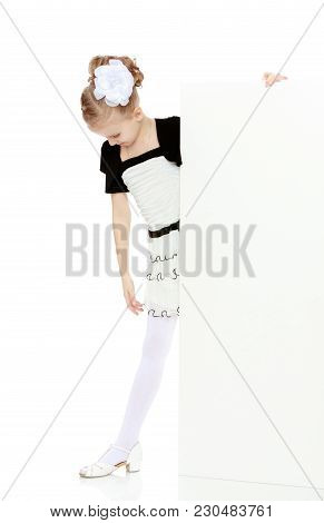 Beautiful Little Blonde Girl Dressed In A White Short Dress With Black Sleeves And A Black Belt.the