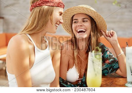 Shot Of Happy Female Wears Fashionable Summer Hat And Blouse Spends Recreation Time With Close Frien