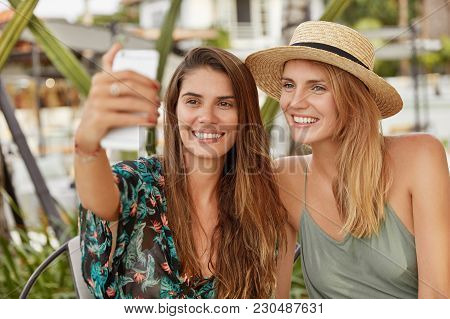 Happy Beautiful Females With Broad Smiles Pose For Selfie While Sit Together In Cozy Exotic Cafteria