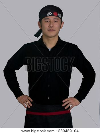 Asiatic cook portrait wearing a black bandana with Chinese word ( Victory ) tradition