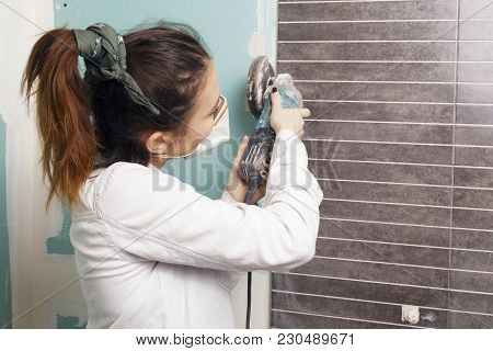 Young Woman Working With A Angle Grinder.