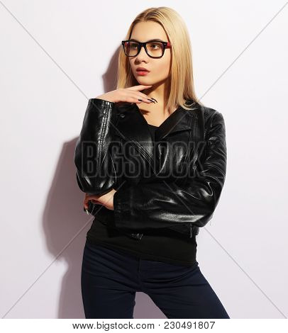 Fashion portrait of young blond  woman. Black leather jacket, pa