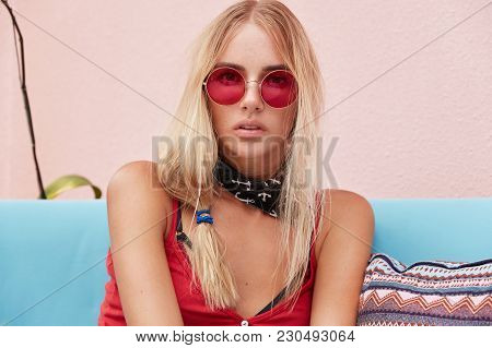 Portrait Of Serious Female Model Looks Directly Into Camera With Mysterious Expression, Wears Trendy