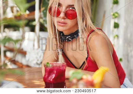 Cropped Shot Of Pleasant Looking Blonde Woman In Trendy Shades, Enjoys Fresh Smoothie In Cafe, Has S