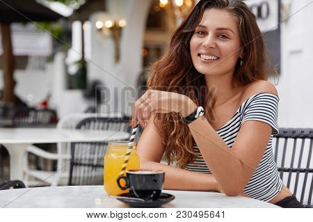 Satisfied Young Woman With Pleasant Appearance Recreats At Coffee Shop, Happy To Spend Summer Holida