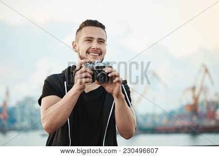 Photojournalist Likes His Work. Portrait Of Happy Pleased Handsome Photographer Smiling Broadly Whil