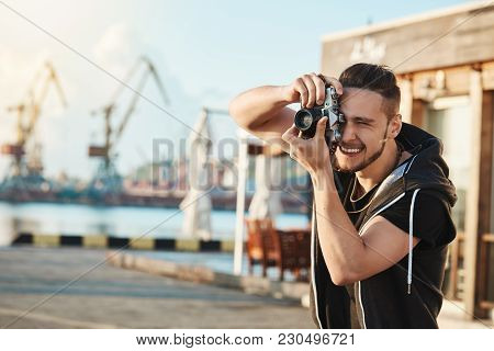 Attractive Young Male Photographer Walking Along Harbour, Making Photos Of Cool Yachts And People, L