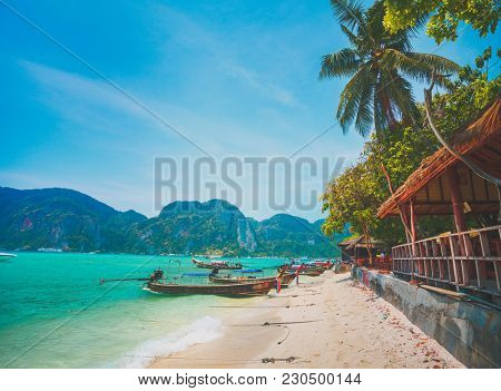 Wonderful scenery the cozy local village and the ocean shore with fishing boats on the limestone cliffs background. Idyllic place for the rest and relax. Phi Phi islands, the Kingdom of Thailand.