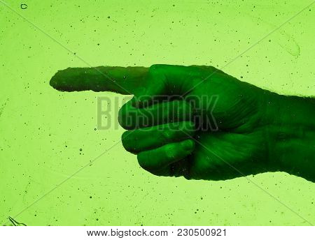 Left Pointed Finger Behind A Pane Of Weathered Vintage Green Glass With Bubbles And Scratches. Poten