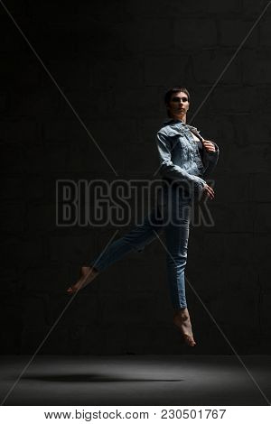 Ballet Dancer With Shot Haircut In Jeanswear Jumping Gracefully In Dark Room