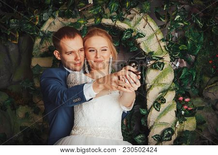 Beautiful Bride In A White Dress And A Young Groom In A Blue Suit Indoors In The Studio During A Pho