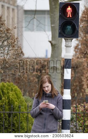 Young Woman Waits At A Traffic Light That Is On Red But Does Not Pay Attention To The Traffic Becaus