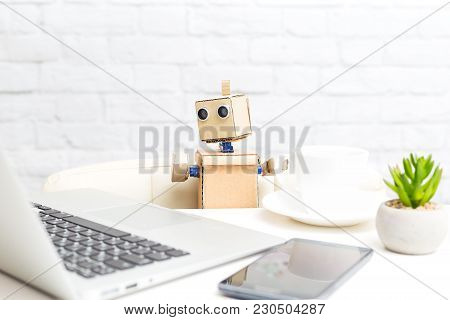 The Robot Is Sitting At The Table And Next To The Laptops With The Phone. Artificial Intelligence